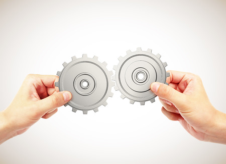 business connection: hands connecting gears on a gray background