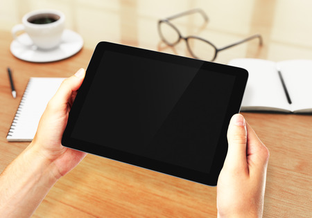Hands holding digital tablet in the workplace