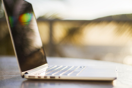 field depth: Modern laptop at sunset, shallow depth of field Stock Photo
