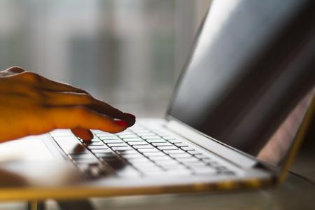 Manos femeninas que pulsan en la computadora portátil, la profundidad de campo Foto de archivo - 39669885