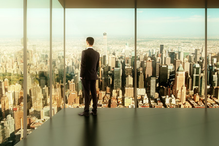 find out: businessman in modern office with a view of the city