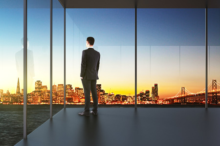 find out: businessman in the office looking over the city at sunset