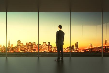 空のオフィスのビジネスマンが窓に立っています。
