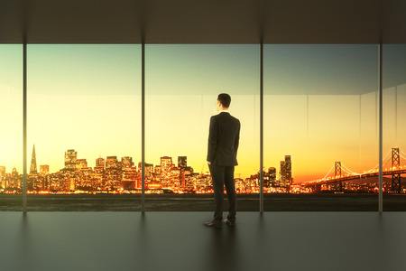 looking out: Businessman in empty office stands at the window Stock Photo