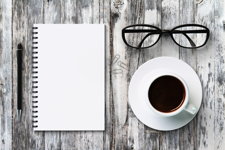 diary: Blank diary, pen, glasses and coffee cup on a vintage wooden table Stock Photo