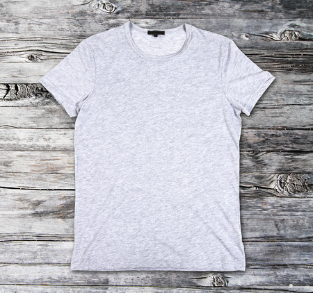 tshirts: Blank gray t-shirt on a wooden surface