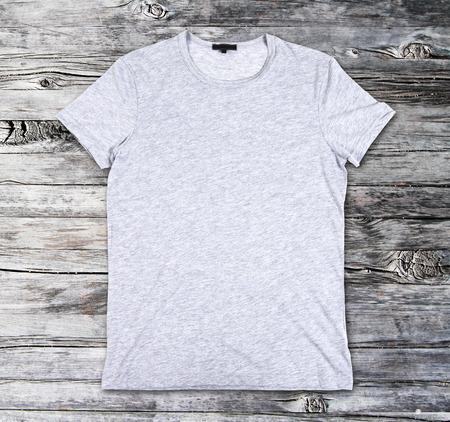 ropa casual: En blanco camiseta gris sobre una superficie de madera