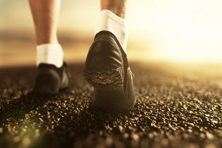 piernas hombre: Corredor piernas en el camino al amanecer, de cerca Foto de archivo