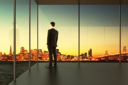 view window: Businessman in empty office stands at the windows Stock Photo