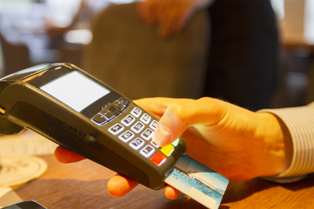 mans hand with credit card swipe through terminal Stock Photo