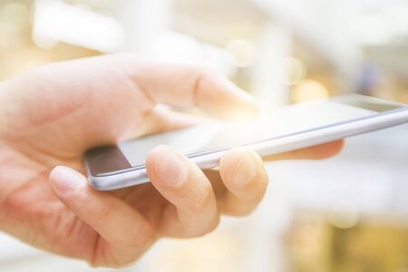 man on cell phone: hand with cell phone on a blurred background Stock Photo