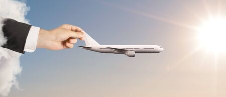 away travel: hand holding white airplane in blue sky