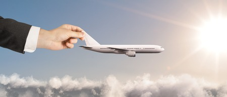 away travel: businessman hand holding white airplane in sky