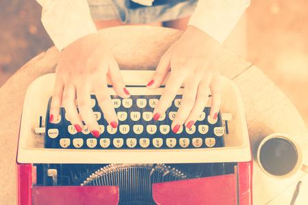 persona escribiendo: Muchacha en la tipificaci�n mesa en una m�quina de escribir, efectos de fotos de �poca Foto de archivo