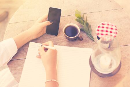 write background: young girl writes in a notebook with cell phone and cup of coffee, vintage photo effect