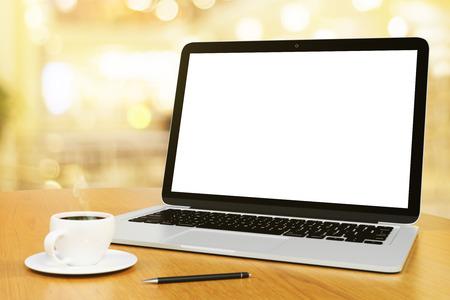 一杯のコーヒーとペン、モックアップとラップトップの空白の画面