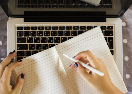hand pen: girl writes in a notebook, with laptop