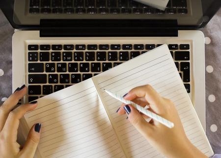persona escribiendo: muchacha escribe en un cuaderno, con el portátil