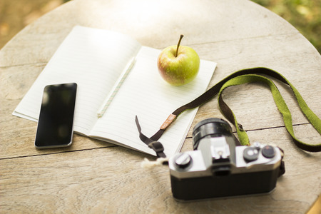 old diary: cell phone, diary, old camera and green apple Stock Photo