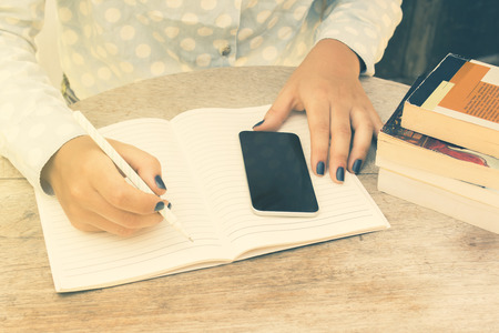 univercity: girl writes in a notebook, with cell phone and books