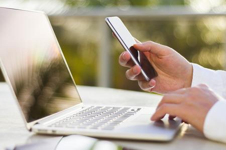 携帯電話とラップトップの朝で実業家 写真素材