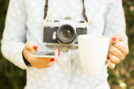 female photographer: girl with cell phone, cup of coffee and old camera