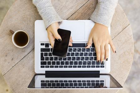 mecanografía: Muchacha con el teléfono móvil, ordenador portátil y una taza de café Foto de archivo