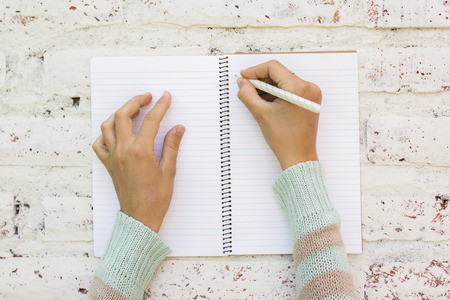person writing: Girl writes in notebook