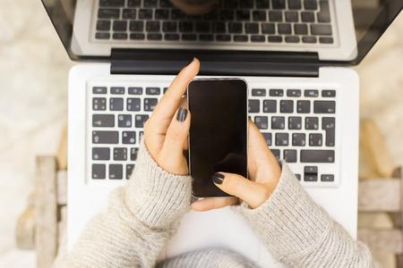 trabajando en casa: Muchacha con el tel�fono celular y la computadora port�til