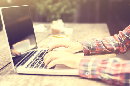 woman typing: woman typing on a laptop at sunrise Stock Photo