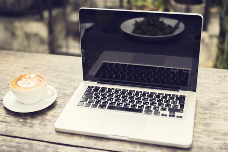 notebook computer: Laptop and cup of cappuccino on a wooden table Stock Photo