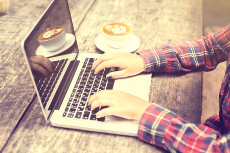 outdoor cafe: Girls hands with laptop and coffee mug on a wooden table Stock Photo