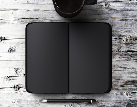 Blank black diary with pen and a cup of coffee on a wooden table Stock Photo