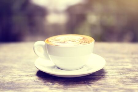 cappuccino cup: Cup of cappuccino on a table, vintage photo effect