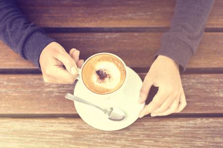 mujer tomando cafe: Muchacha que sostiene una taza de capuchino y mesa de madera Foto de archivo