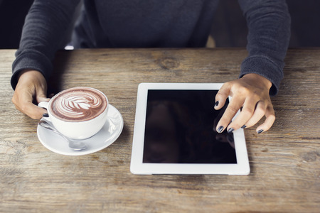 blank tablet: Girl hands with digital tablet and cup of coffee on a wooden table