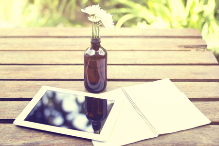 blank tablet: Blank diary with digital tablet and flowers on a wooden table outside Stock Photo