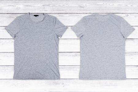 blank t shirt: Two gray blank T-shirts on a white wooden background Stock Photo