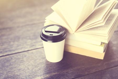 conocimiento: Café para llevar y el paquete de libros sobre una mesa de madera, efecto de la foto de la vendimia