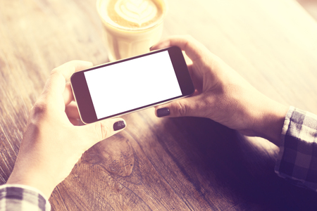 lady on phone: Girl hands with blank smatphone and cup of coffee on a wooden table, vintage photo effect