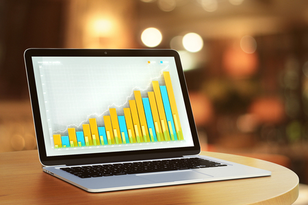 oficina: Laptop con gráfico de negocios en una mesa en un café