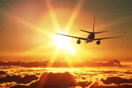 voyage avion: Avion est en train de décoller au coucher du soleil Banque d'images