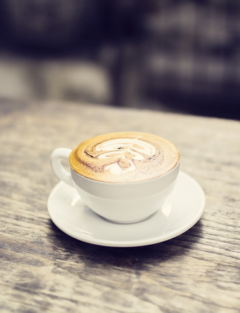 cappuccino cup: Cup of cappuccino on a wooden table