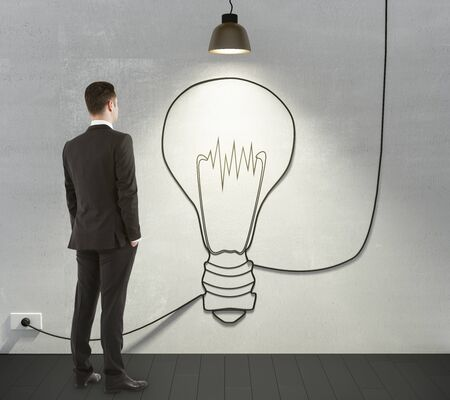 electrical wires: Man looking to the light bulb concept on the wall