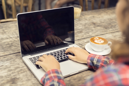 Hipster girl hands, laptop and coffee mug on a wooden table
