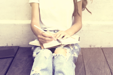 wrote: Schoolgirl sitting on floor and wrote in a diary