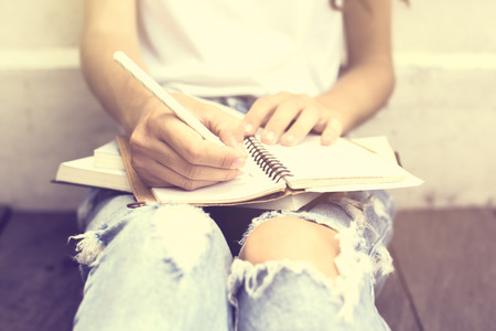 journal: Girl sitting on floor and wrote in a diary Stock Photo
