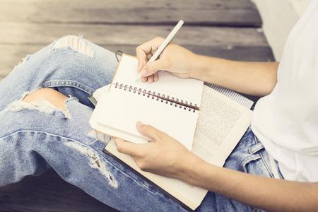 Meisje zittend op de vloer en schreef in een notitieboekje Stockfoto