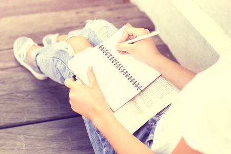 writing a letter: Schoolgirl sitting on floor and wrote in a notebook
