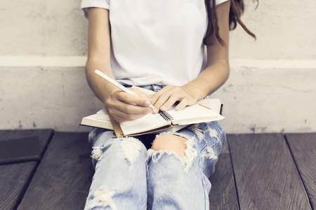 Mädchen machen Notizen im Tagebuch und sitzt auf einem Holzboden